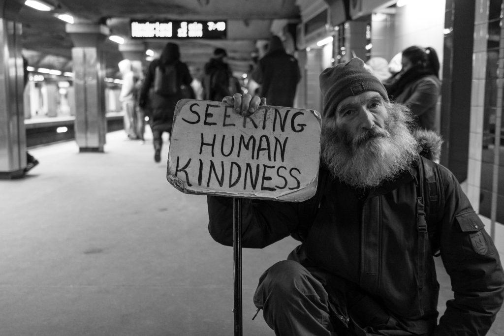 como ajudar as pessoas - homem com placa pedindo bondade